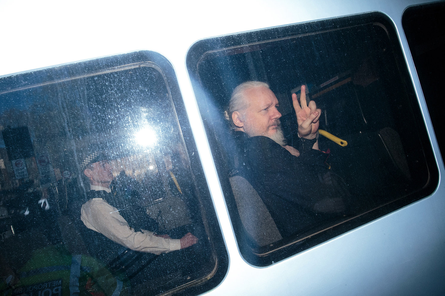 Julian Assange gestures to the media from a police vehicle on his arrival at Westminster Magistrates court on April 11, 2019 in London.