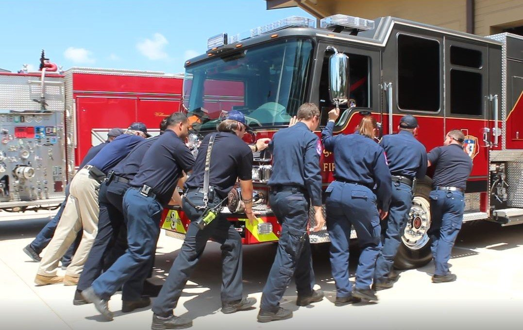 Members of the Sam Bass Fire Department push the first fire truck into the new Sam Bass Fire Station 3 in Round Rock during a grand opening ceremony on May 16, 2019.