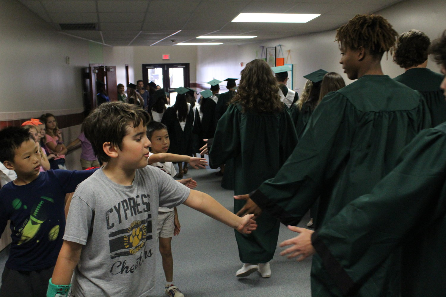 Brandon Brown, a student at Cypress Elementary School, high-fives graduating seniors from Cedar Park High School on May 29, 2019.