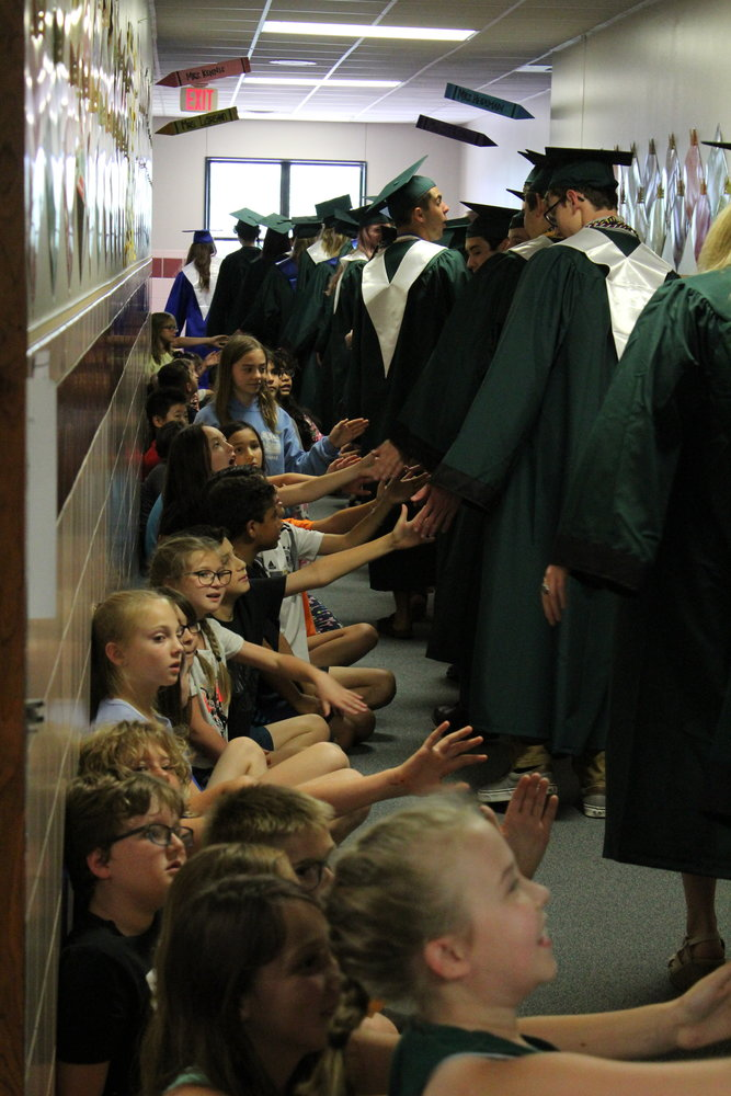Students from Cypress Elementary School attempt to give high-fives in the hallway to graduating seniors from Cedar Park High School during a 'senior walk' on May 29, 2019.