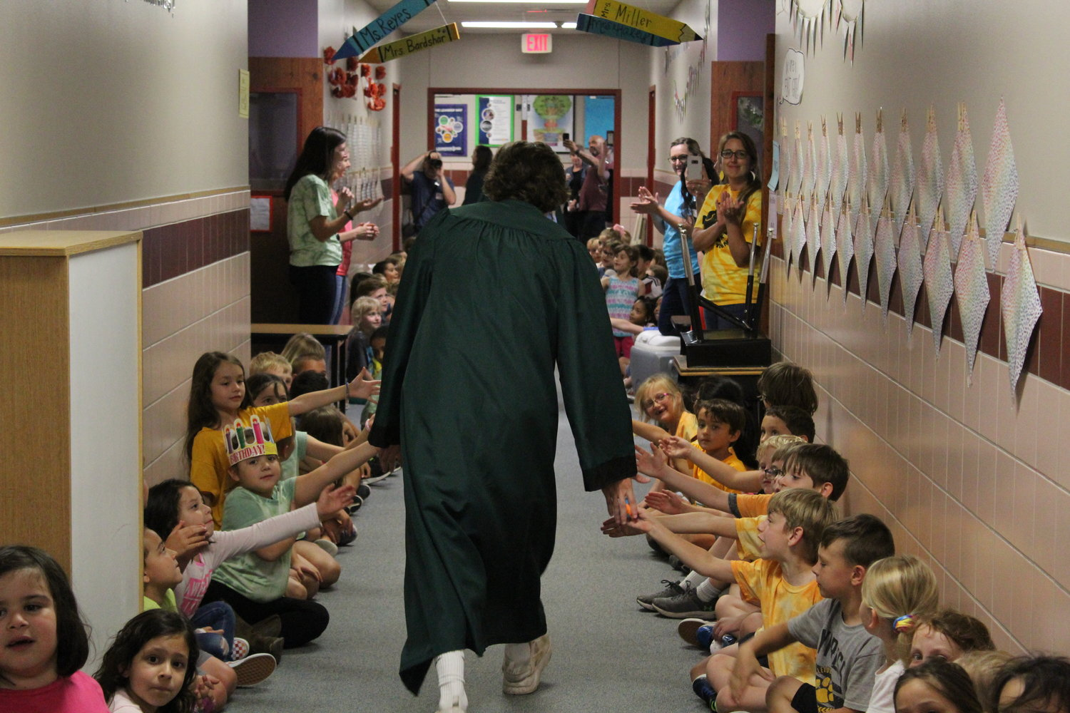 A senior from Cedar Park High School high-fives students from Cypress Elementary School while running to rejoin the line of seniors on May 29, 2019.