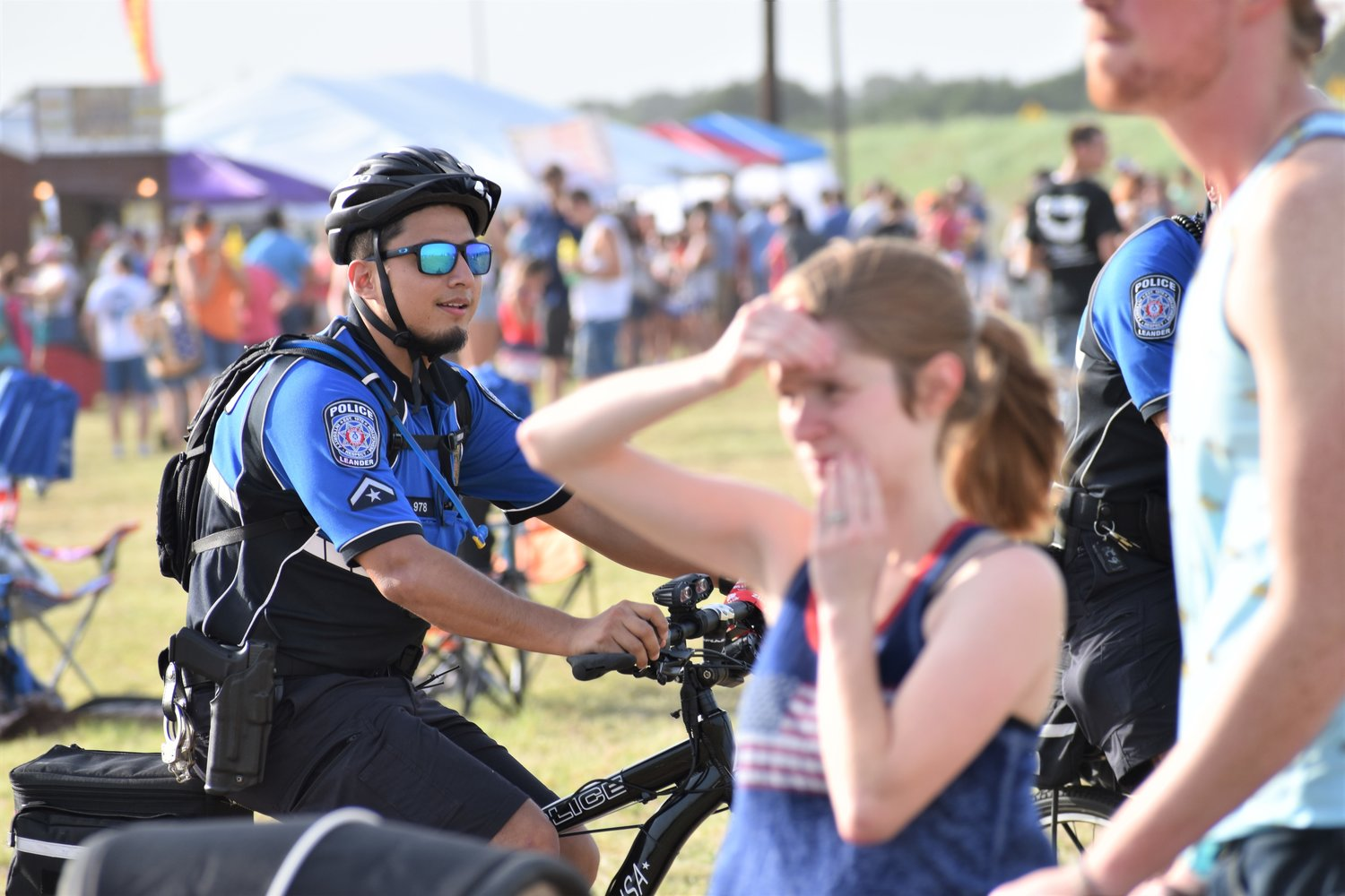 A police officer rides around the festival grounds on a bicycle during Liberty Fest in Leander on Thursday.
