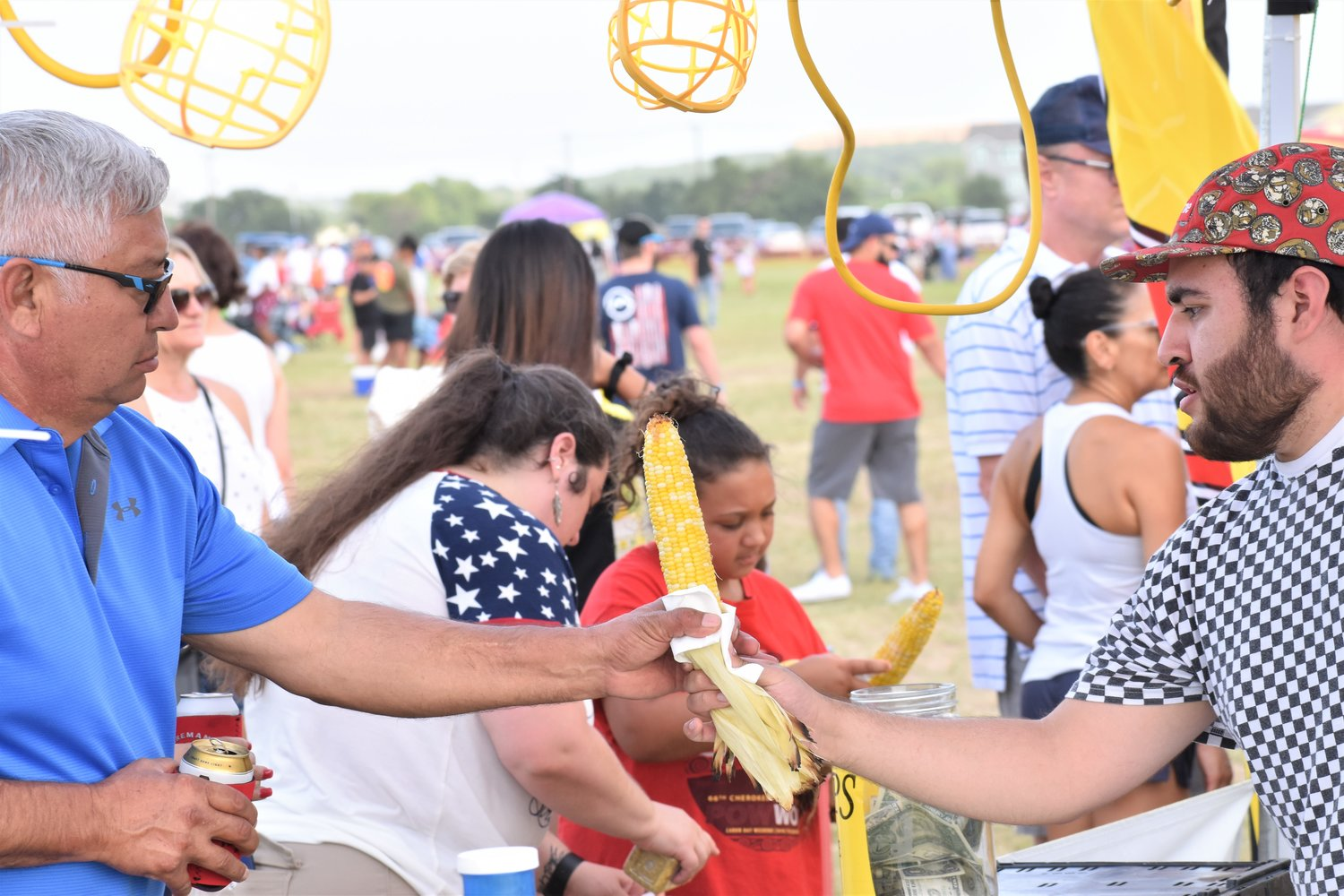James Ramirez, of the RJ Roasting booth, serves roasted corn to an attendee of Liberty Fest in Leander on Thursday.