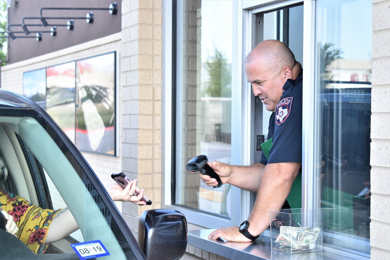 Officer Ray Killebrew scans a customer's phone during the Coffee With A Cop event on Monday. He was tasked with helping out in the Starbucks drive-thru along with another officer.