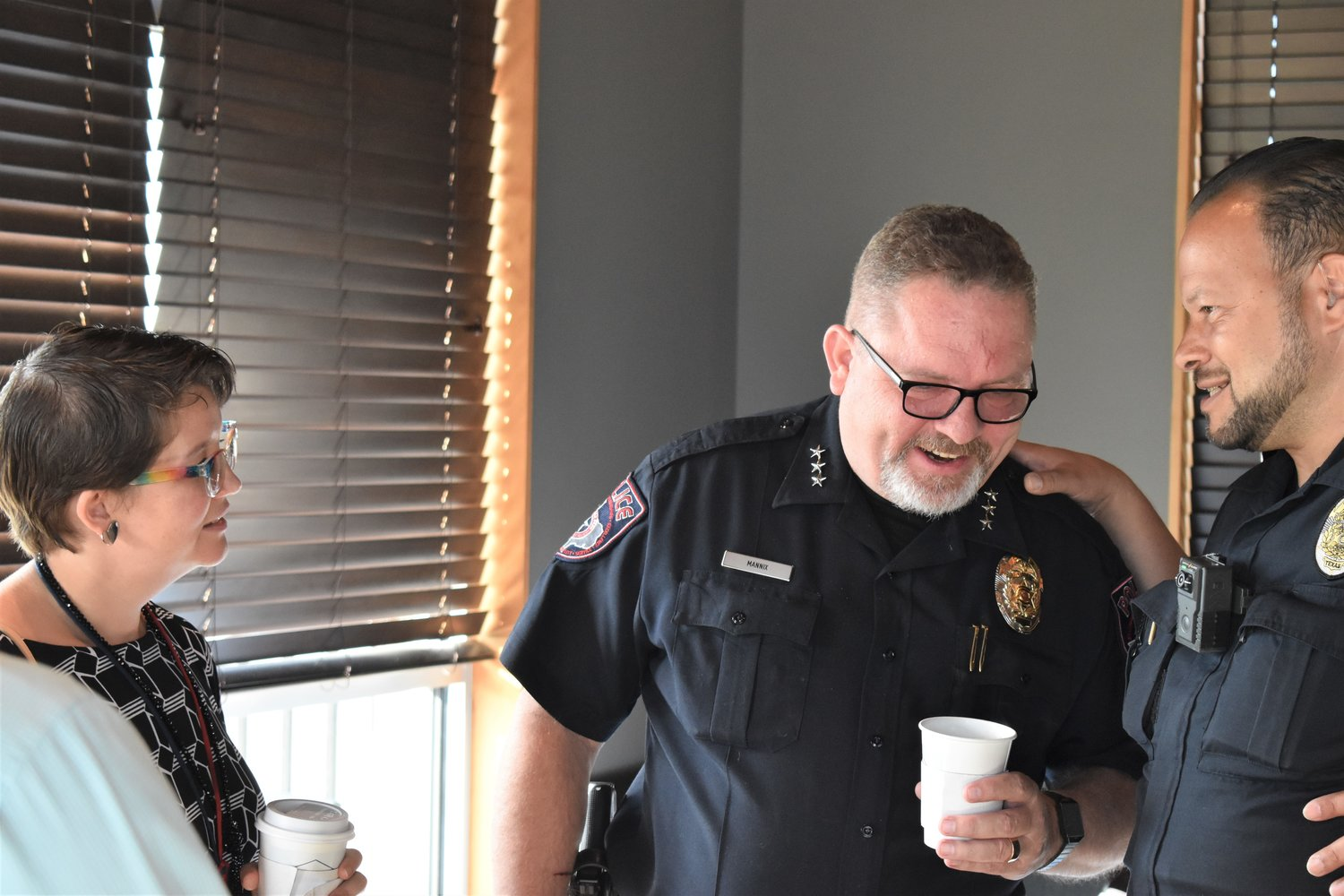 Cedar Park Police Chief Sean Mannix  laughs at an aside by Cedar Park police officer David Camacho while they speak with residents as part of the Coffee With A Cop event.