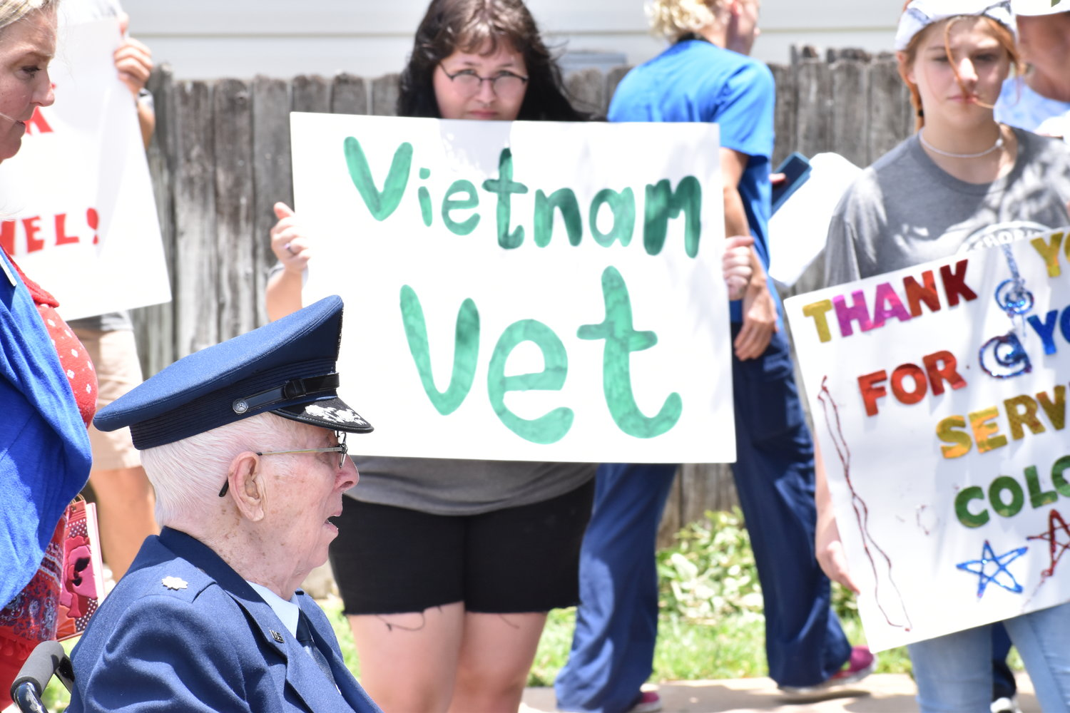 Lt. Col. Jerry Jennings is wheeled past attendees with supportive signs before taking pictures with family, staff and supporters.