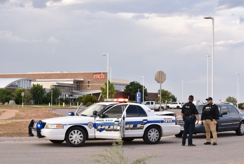 Law enforcement officers stand outside the movie theater in Odessa where a gunman was killed in a shootout with police.