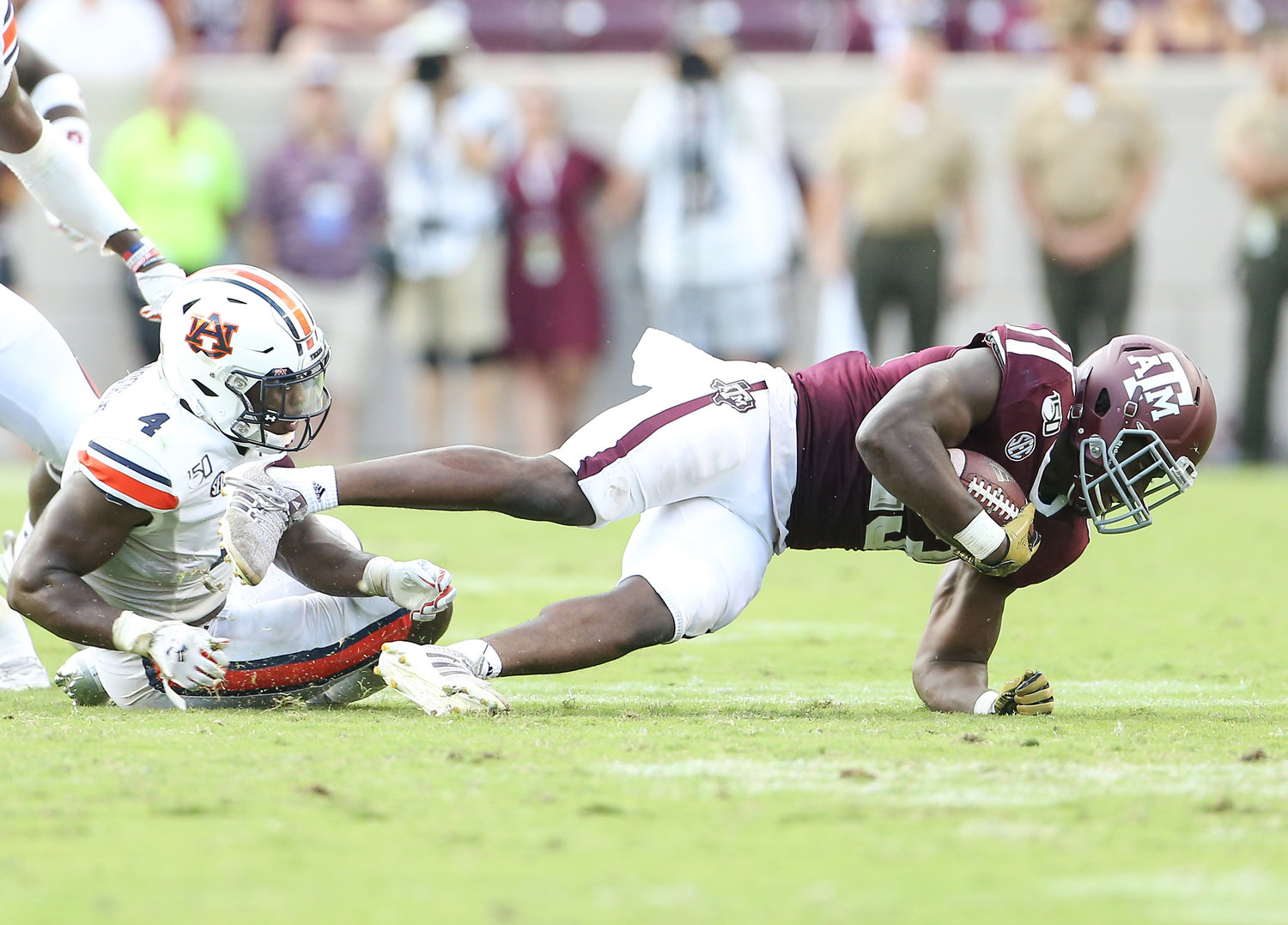 Texas A&M Aggies running back Jacob Kibodi (23) is brought down by Auburn Tigers defensive back Noah Igbinoghene (4) during an NCAA football game between Texas A&M and Auburn at Kyle Field in College Station, Texas, on September 21, 2019.