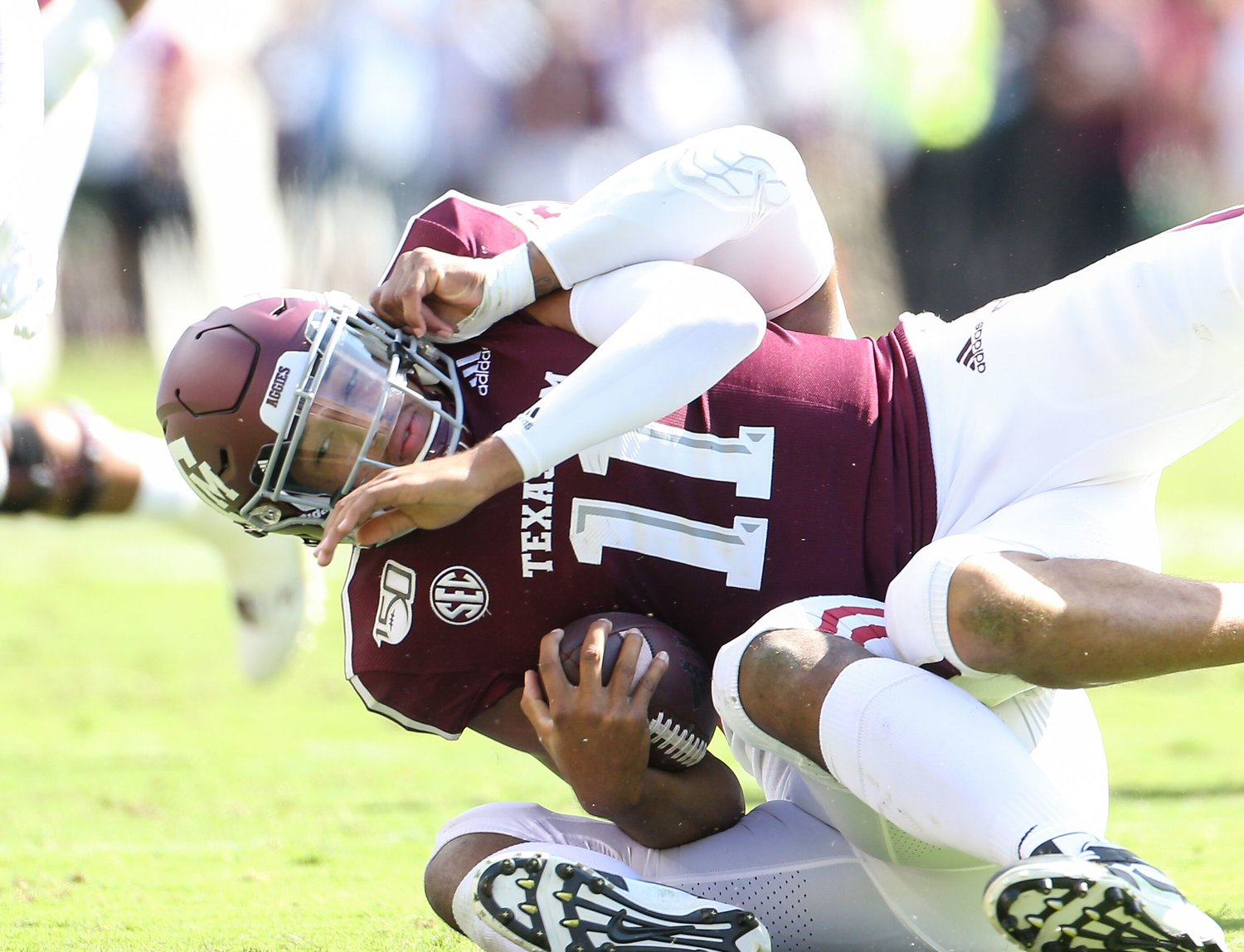 Texas A&M quarterback Kellen Mond is dragged to the turf by an Alabama defender during Saturday's home loss to the Crimson Tide.