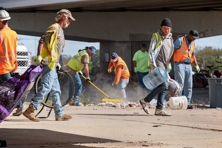 Texas Department of Transportation workers remove trash and personal belongings from a homeless encampment under Highway 290 at Westgate Blvd on Monday.