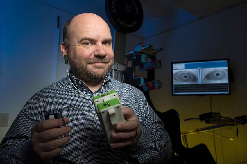 Associate Professor of Pharmacology Physiology and Neuroscience Jorge Serrador holds stochastic noise sub sensory stimulator