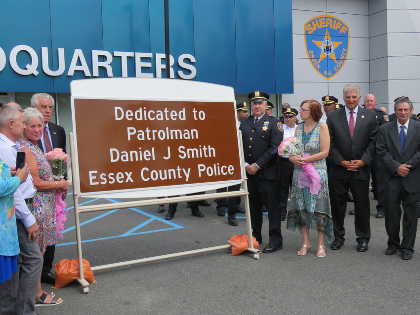 "Essex County Executive Joseph N. DiVincenzo, Jr. (right) and Essex County Sheriff Armando Fontoura (left) joined with family members and friends of the late Office Danny Smith and law enforcement officers from around Essex County to announce the dedication of the ""Patrolman Daniel 'Danny' J. Smith Memorial"" on Wednesday, August 28th.     A native of Bloomfield and a member of the old Essex County Police Department, Patrolman Smith was fatally shot on September 17, 1984, while making a routine traffic stop on Interstate Route 280.     The highway marker dedicates a portion of Route 280 in Patrolman Smith's memory. The section of the highway is between mile marker 11.1 near the Oakwood Avenue overpass to mile marker 12.4 in East Orange. (Photo courtesy of Essex County)"