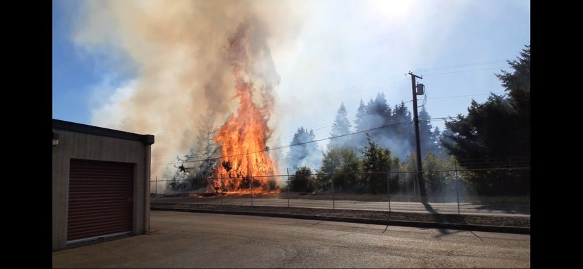 Firefighters from the Tumwater Fire Department responded to a fire by a storage facility off of Interstate 5 late Tuesday. The fire was caused by a boat that fell off a trailer, which caused dry grass and trees on the side of the road to start burning. Officials from other fire departments also responded to the incident.