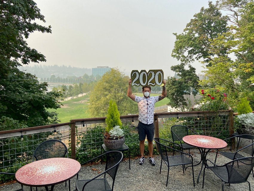 Contrasting today's smoky atmosphere against the same view just over two weeks ago, Swing Wine Bar bartender John Swetz holds a sign previously used to optimistically welcome the New Year.