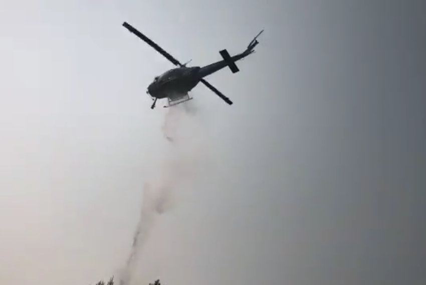 A Department of Natural Resources helicopter drops water on a fire in the 1300 block of Cooper Point Road Southwest on Sept. 11.