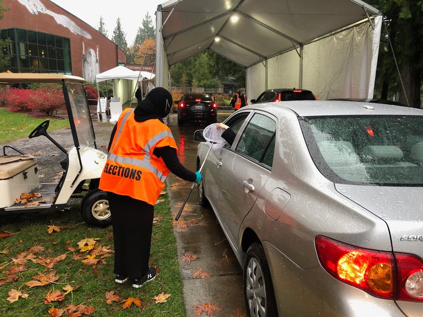 County employee Shukri Abdulahi uses a butterfly net to deliver a last-minute ballot to a voter today at 4 pm at the voting center.