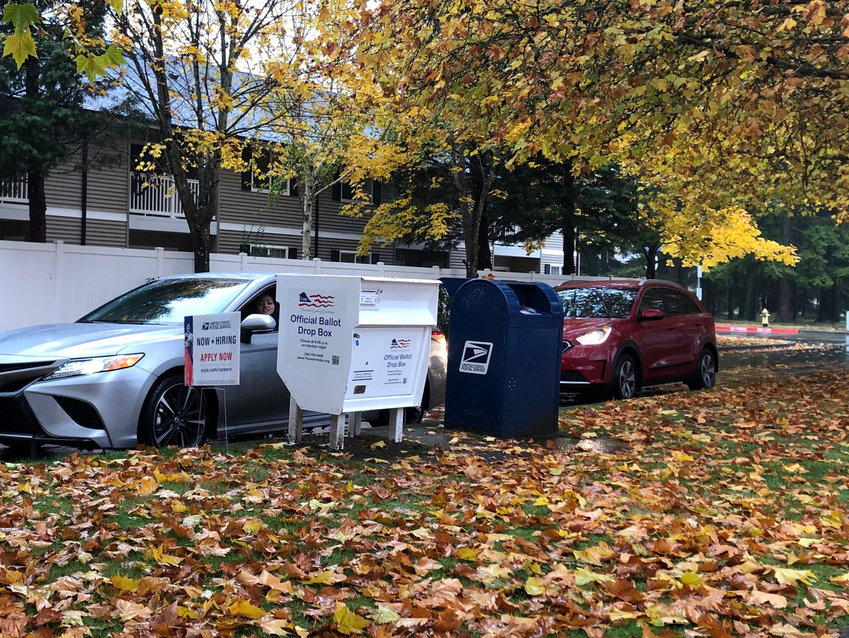 A driver deposits her ballot in the official drop box across the street from the U.S. Post Office in Lacey on Election Day last year.