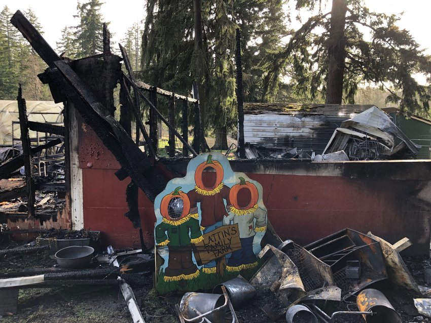 Four generations of children have posed behind photoboards at Lattin's Country Cider Mill and Farm south of Olympia. This one, standing just two feet next to the barn, survived the fire on January 12, 2021.