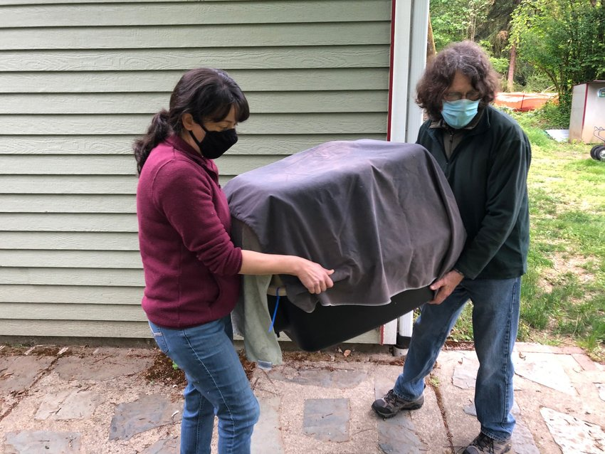 This sequence shows the bald eagle being carried from the vehicle in which it was transported back to the property where it was found, on Sun., May 23, 2021, just prior to its release. L-r, Stephanie Estrella, Mark Fleming.