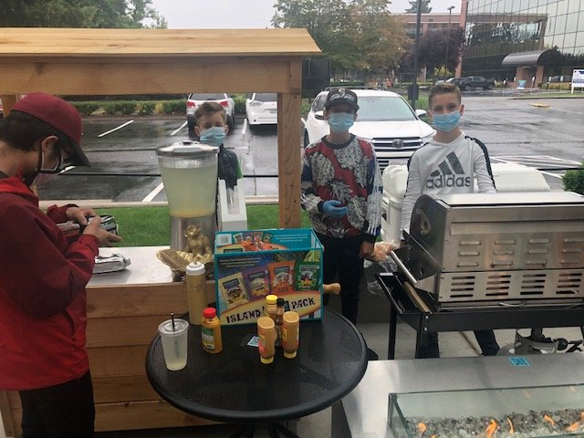 L-r, Lemonadier-partner Colby Ames, 10, is assisted by friend-employee Raleigh Garcia and business partner/barbequer Royce Nelsen as they serve a customer on a rainy day in August.