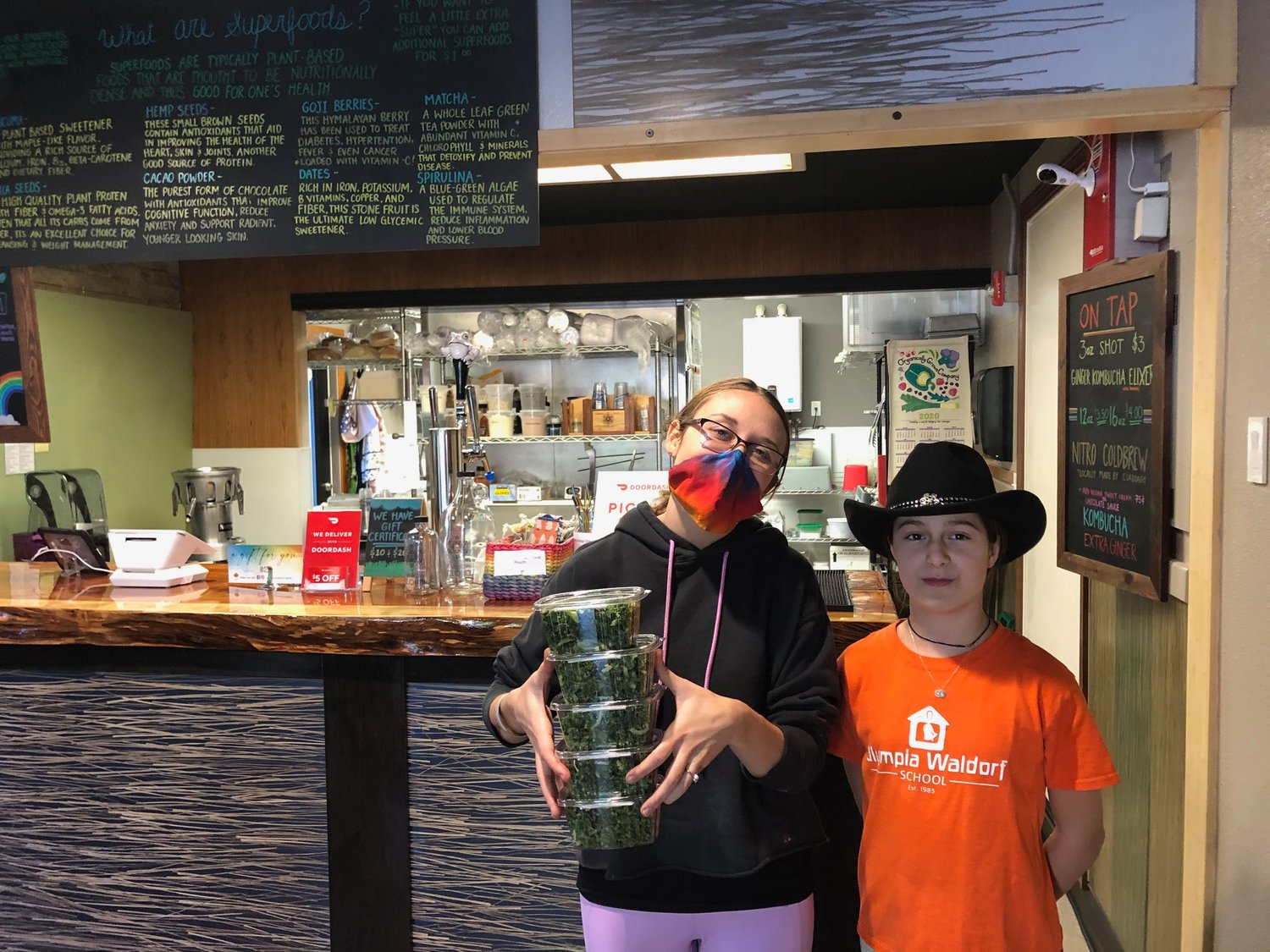 Co-owner Sydney Harmell poses with salads and daughter, Blueberry, in front of the live-edge wood counter at Rainbow Cloud Cafe.
