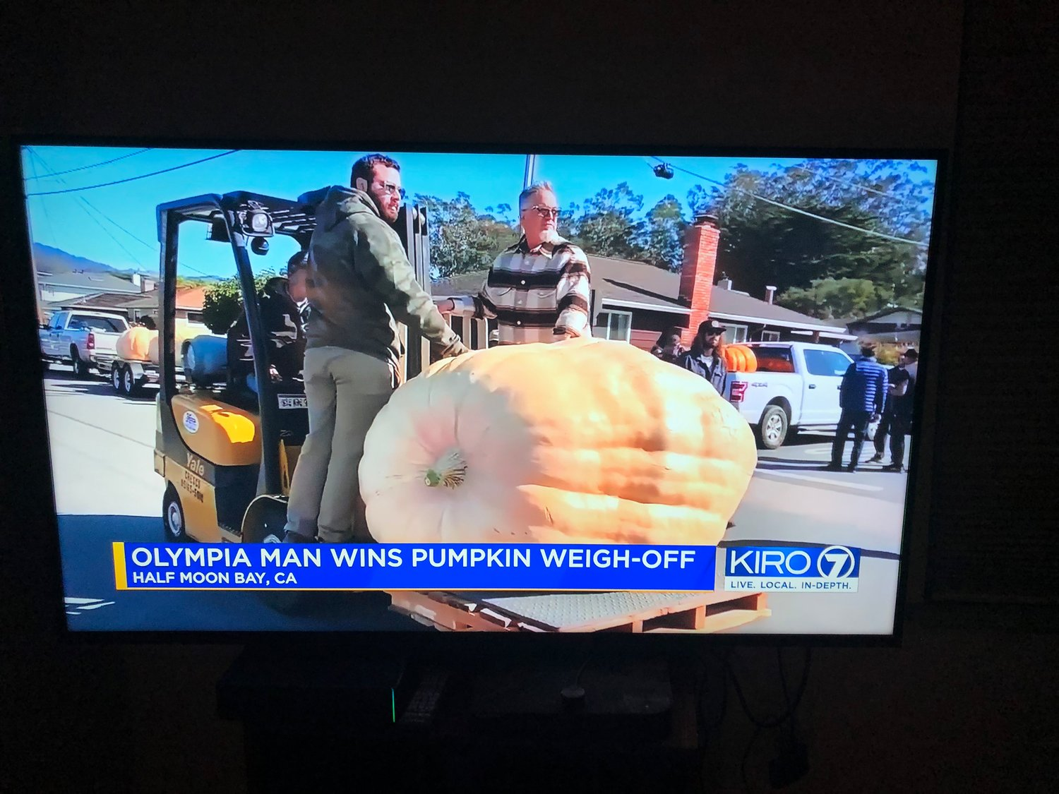 Jeff Uhlmeyer's giant pumpkin is escorted to the weighing platform, as shown on KIRO7 News on Oct. 12, 2021.