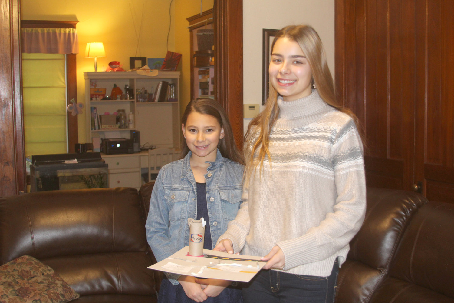 Lilou Beachy (right) and her 11-year-old sister, Maëlys, show off a rocket pad project Maëlys made in celebration of Lilou being named a national semi-finalist in the Name the Rover contest.
