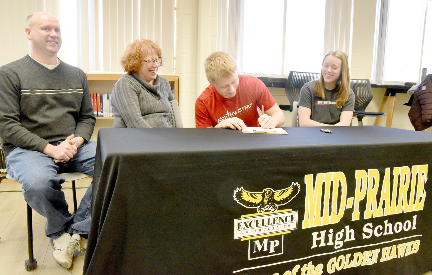Brad Tornow signs his letter of intent while his sister, Abby, and parents David and Sherry look on Tuesday morning.