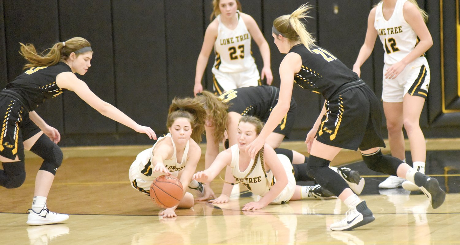 Lone Tree's Holley Johnson (left) and Sara Branson dive for a loose ball in the Lady Lions' 49-48 thrilling victory over Louisa-Muscatine.