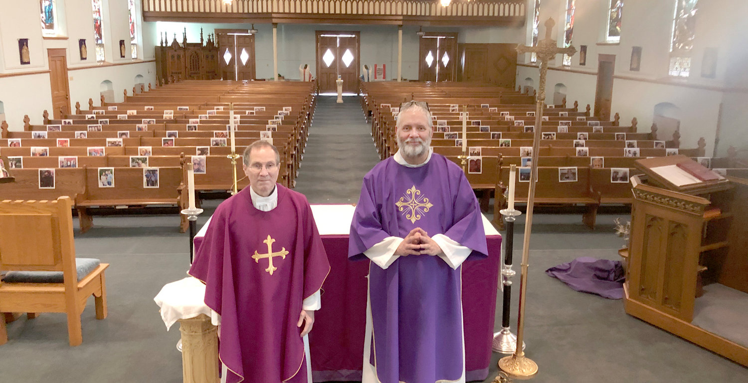 Father Bill Roush (left) and Deacon Derick Cranston prepare to celebrate Mass at St. Mary's Catholic Church. The pews are decorated with photos of parishioners.