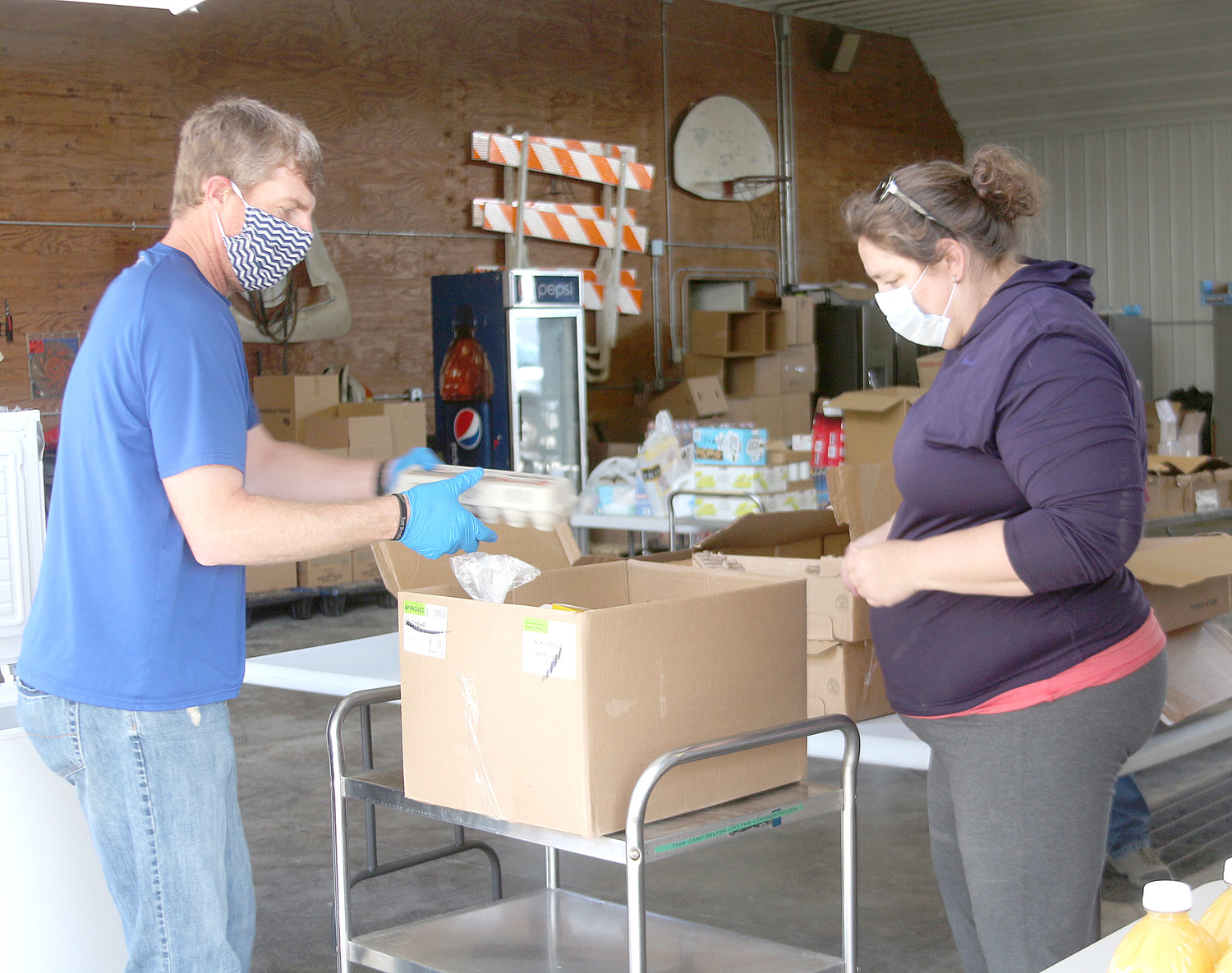 Riverside Mayor Allen Schneider (left) and Mid-Prairie school board member Gabrielle Frederick pack food boxes at the Kalona city shop on Saturday morning.