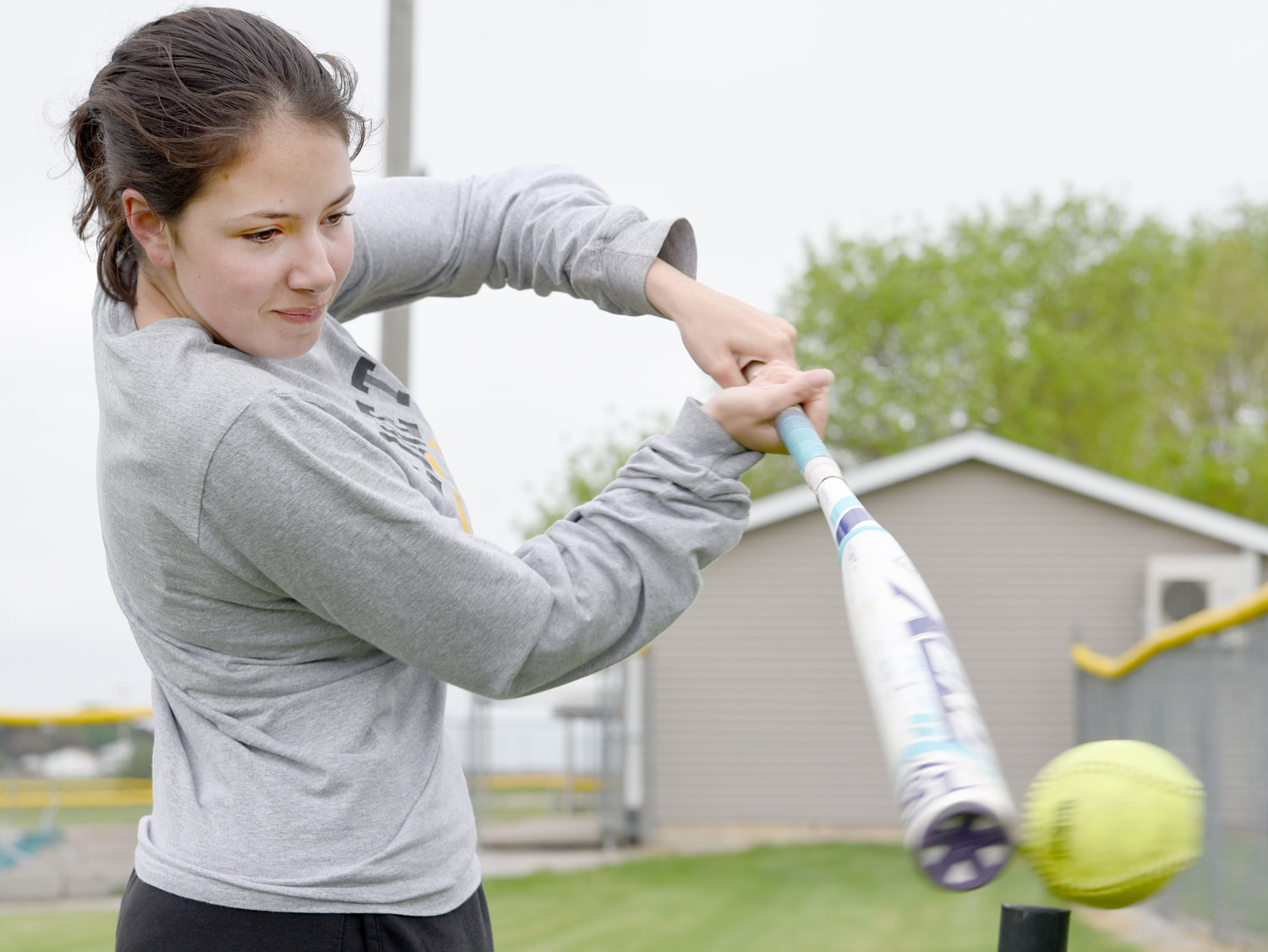 Whitney Willoz hits the softball off the tee. She plays for the Lone Tree Lions.