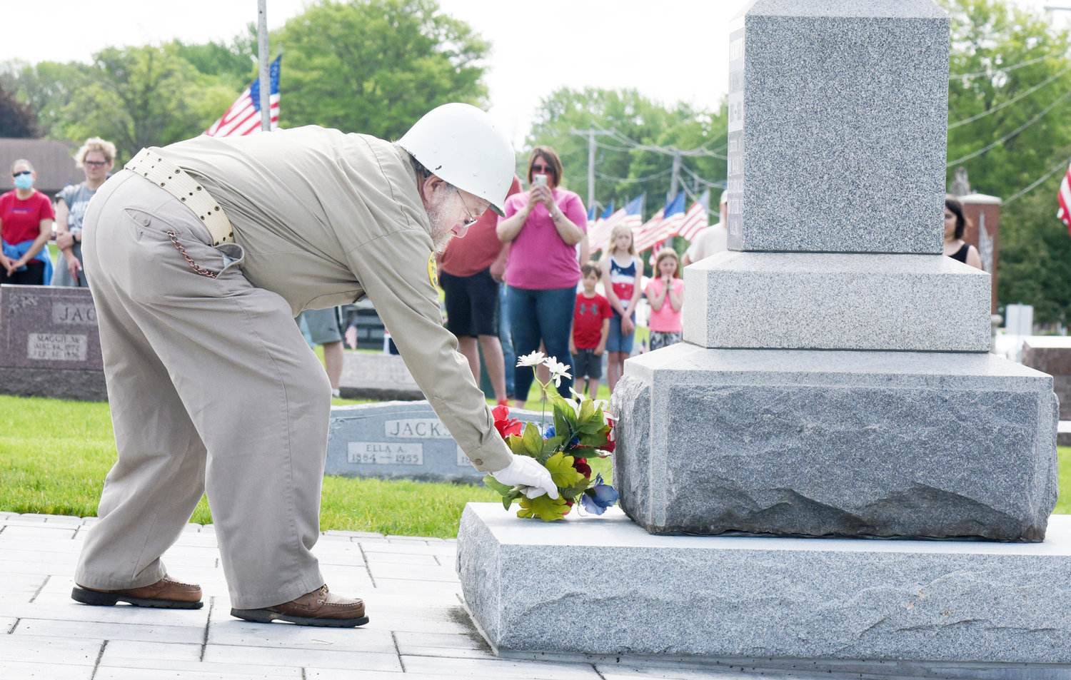 Richmond AmVets Sgt. at Arms Mike Welte lays flowers on the memorial to the unknown dead at Sharon Hill Cemetery.