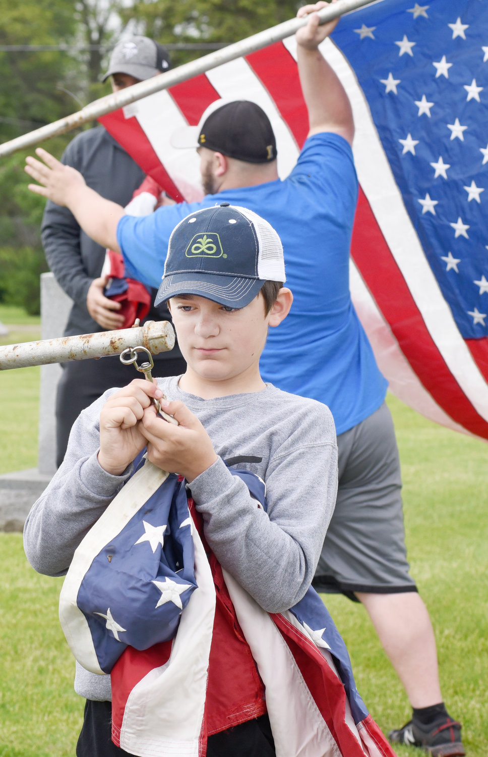 Caedyn Huston fastens a flag to a pole at Sharon Hill Cemetery in Kalona. He was there with sister, Adelyn, and his dad, Michael.