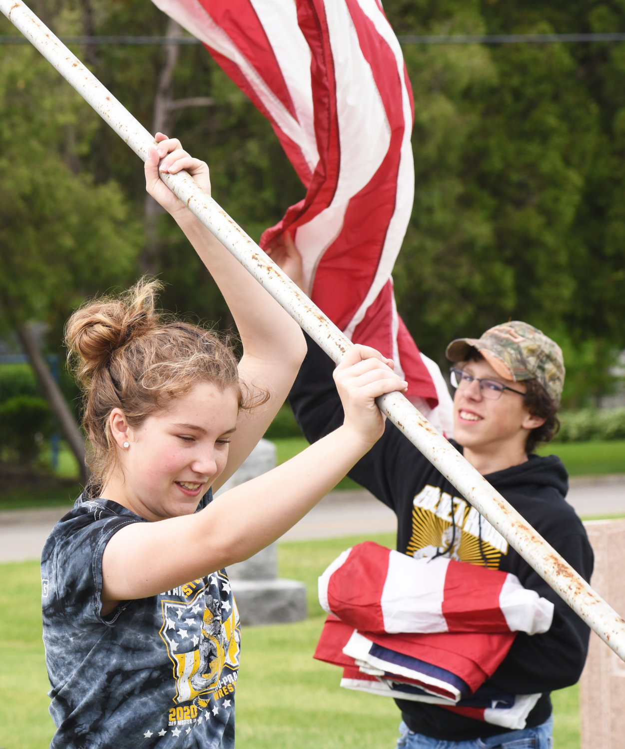 Helpers raise the flags at Sharon Hill Cemetery in Kalona.