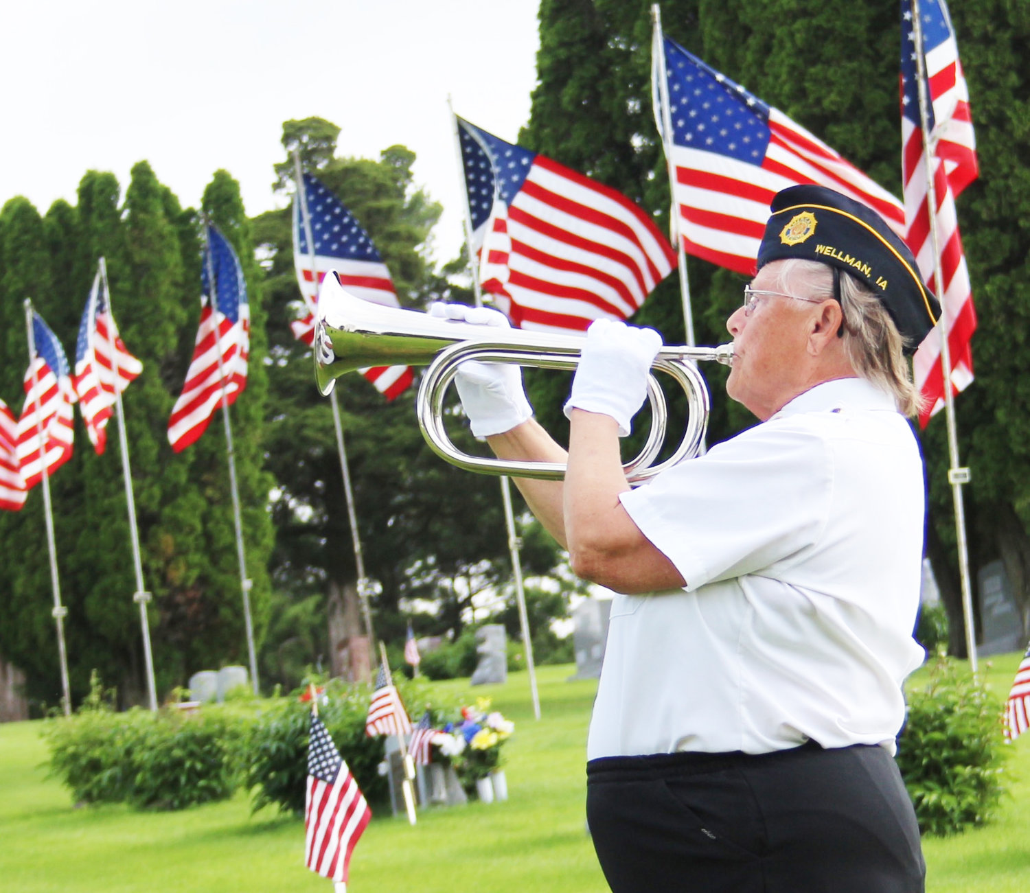 "Donna Fanatia of the Charles Polton American Legion Post No. 427 in Wellman plays ""Taps"" during a brief Memorial Day ceremony at the Wellman cemetery Monday morning."