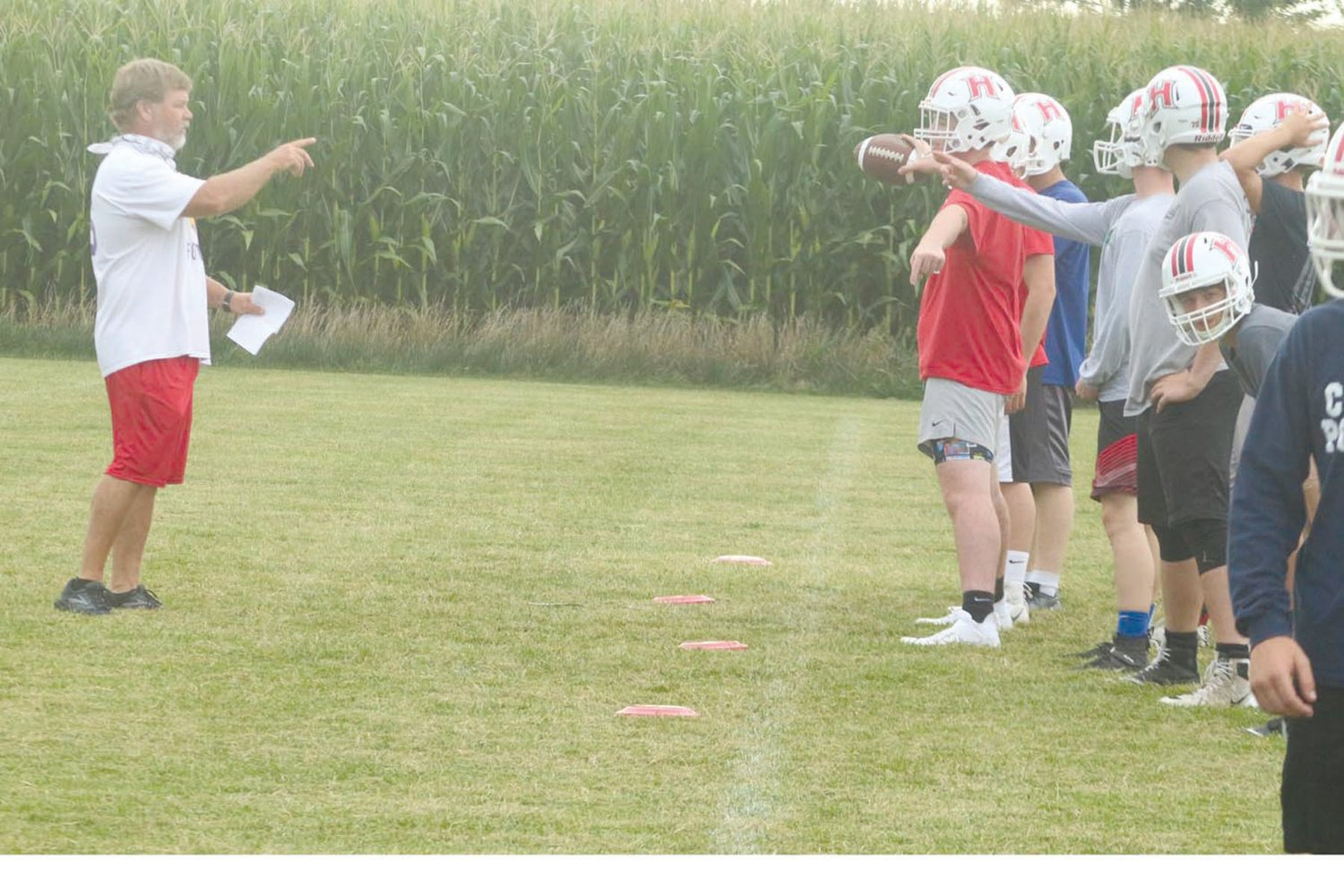 Highland coach Joe Donovan instructs his first offensive unit before running a play in practice Monday.