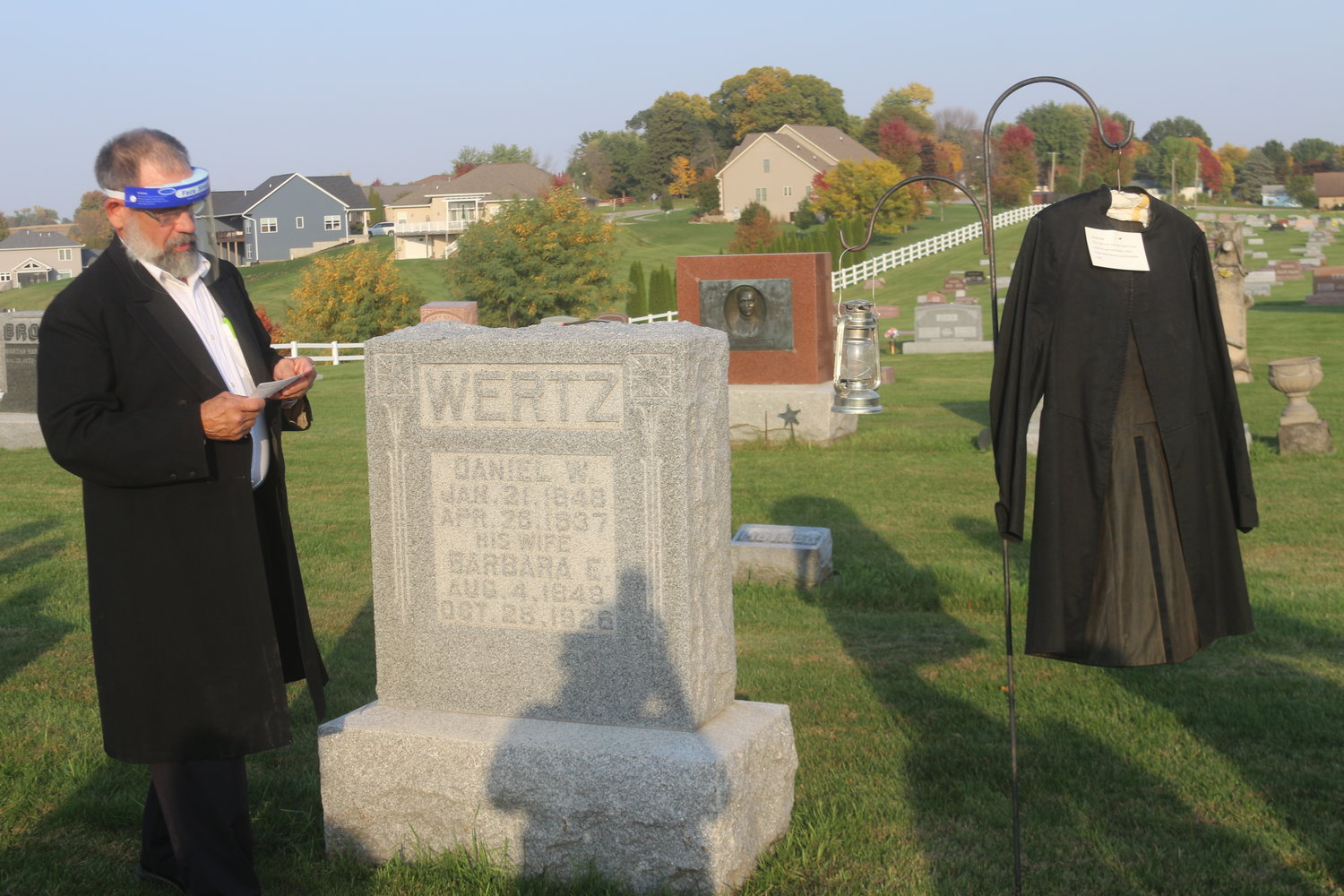 Calvin Yoder portrays one of his ancestors, Daniel Wertz, during the cemetery walk on Oct. 10. Hanging next to the gravestone is the coat Wertz wore during his wedding in 1871.