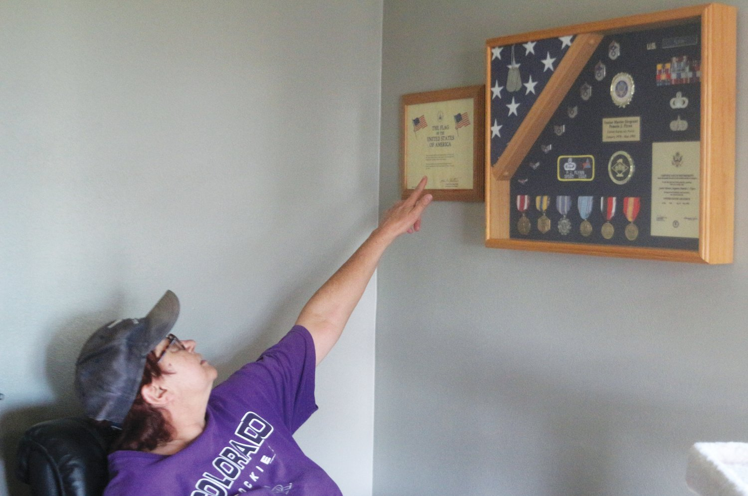 Pam Flynn, who served in the Air Force from 1978-2002 shows off her military achievements, including a flag that flew over the US Capitol building, complete with a certificate of authentication.