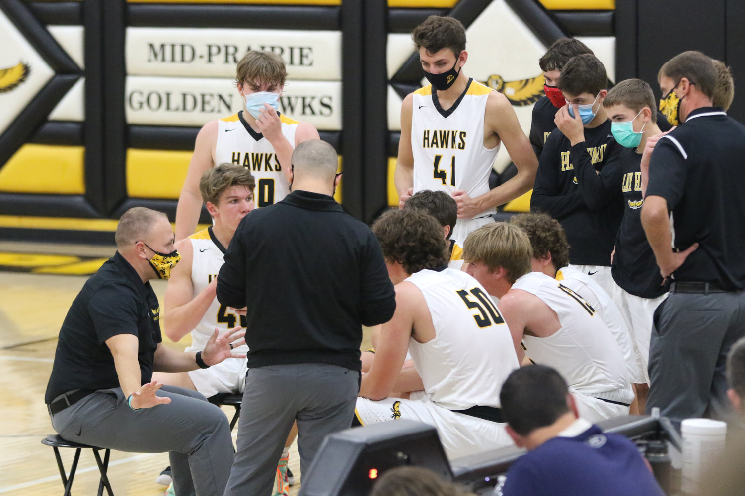 Mid-Prairie coach Daren Lambert (left) addresses his squad after the first quarter of a scrimmage with Mediapolis in Wellman on Saturday, November 21.