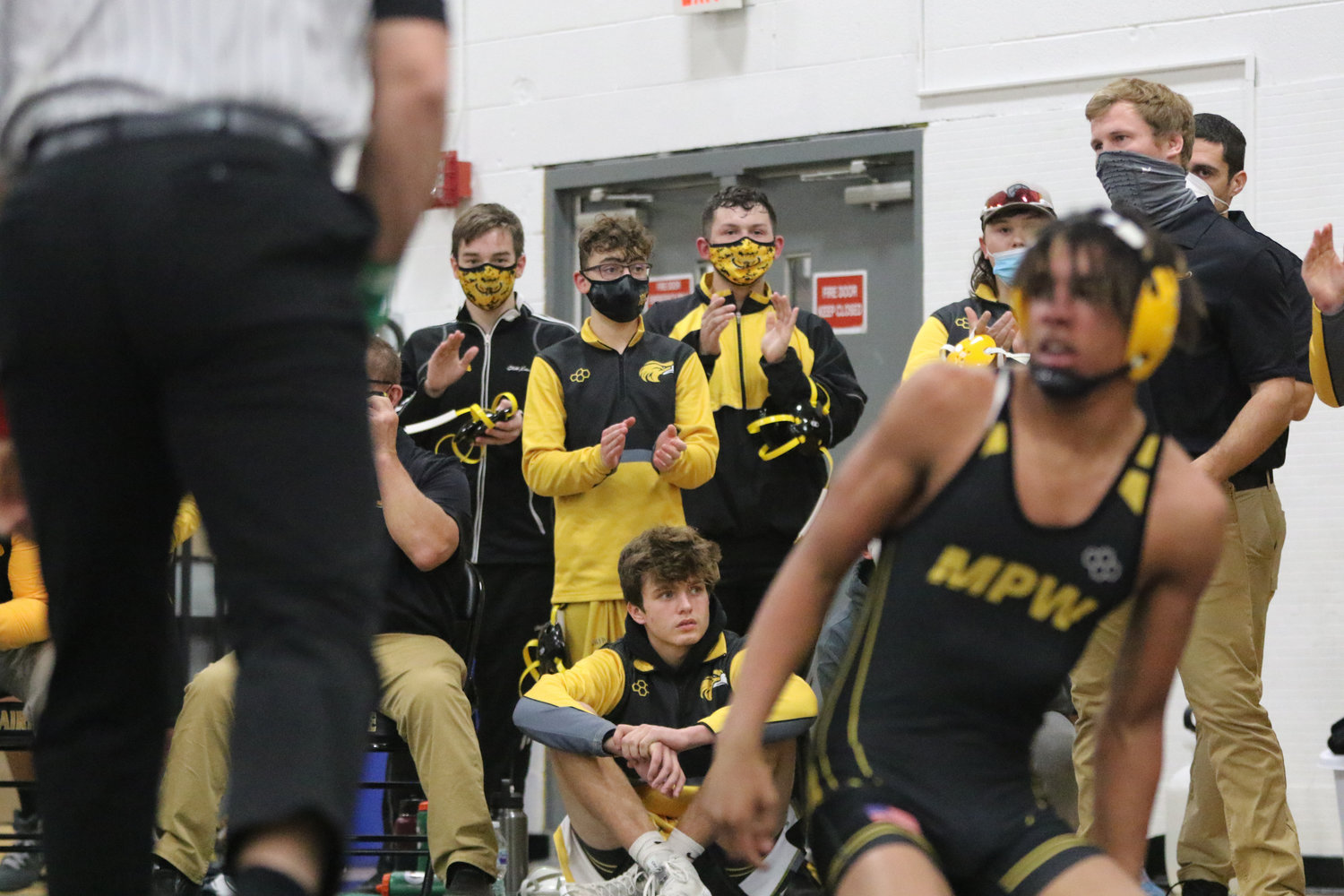 The Mid-Prairie bench reacts to Jardin Mufaume's pin in the first match of the night.