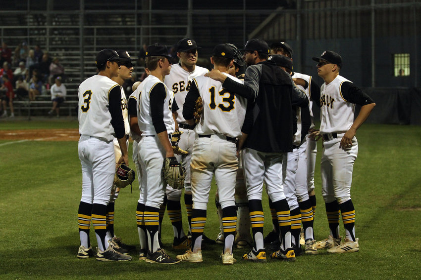 Head coach Dane Bennett (black jacket) created an unbreakable bond with his baseball players, most especially with the eight seniors who played their final game for him in the regional quarterfinal.