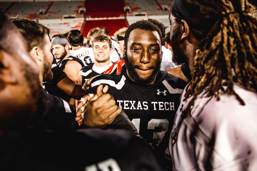Texas Tech senior defensive lineman and former Mayde Creek High standout Malik Essilfie celebrates with teammates after being told he was put on scholarship by the football program after the last practice of fall camp on Aug. 23.