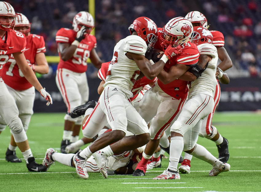 Houston, Tx. Nov. 29, 2019: Katy's Ronald Hoff (34) carries the ball as he's brought down by North Shore defenders during the regional playoff game between Katy Tigers and North Shore at NRG Stadium in Houston. (Photo by Mark Goodman / Katy Times)