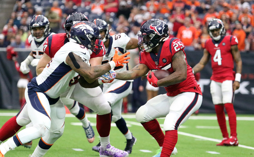 Houston Texans running back Duke Johnson (25) tries to escape from a Denver Broncos defender on Sunday, Dec. 8, during their game at NRG Stadium. The Broncos won, 38-24.