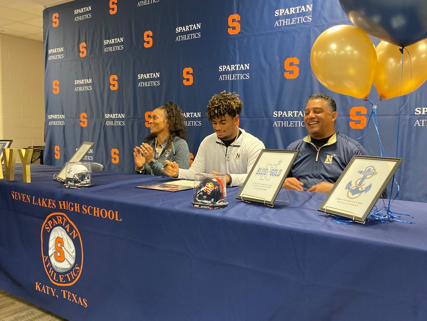 Seven Lakes senior defensive lineman Jaylinn Simon looks at his national letter of intent as his parents mother Shawnie and father Johnny look on during Early Signing Day on Dec. 18 at Seven Lakes High.
