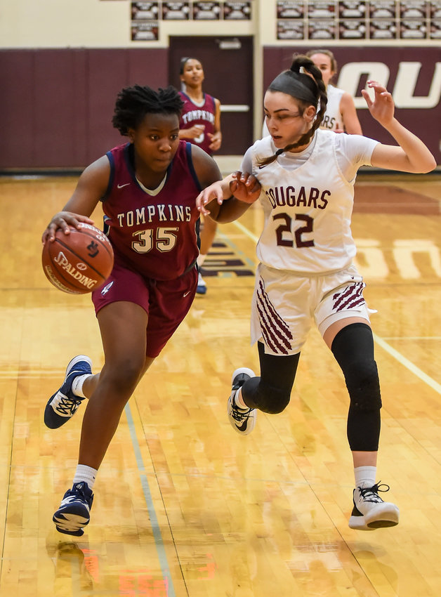 Katy Tx. Jan. 3, 2020: Tompkins' Fiyin Adeleye (35) brings the ball up court guarded by Cinco Ranch's Abby Bala (22) during district basketball game between Tompkins Falcons and Cinco Ranch Cougars at CRHS.  (Photo by Mark Goodman / Katy Times)