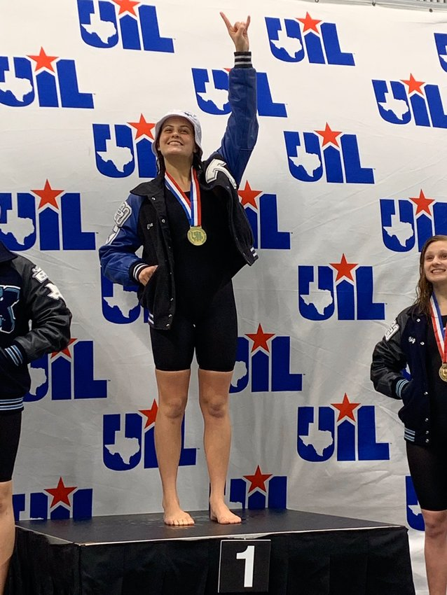 Taylor High senior and future Texas Longhorn Emma Sticklen flashes the 'Hook 'Em' sign after defending her state championship in the 100-yard backstroke at the UIL state swim meet on Feb. 15 in Austin.