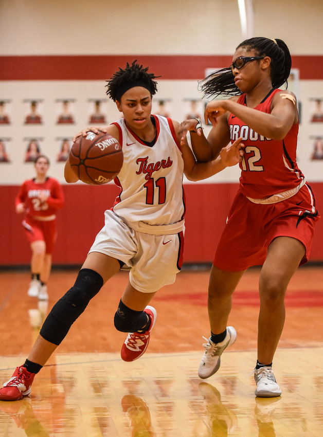 In this file photo from earlier this season, Katy High senior guard Allana Thompson (11) dribbles around Clear Brook's Hailey Henry (12) as she heads to the basket during a game at Katy High. In the Tigers' bi-district playoff game against Fort Bend Bush on Feb. 17, Thompson scored a game-high 20 points, but the Tigers fell short in a 54-39 loss that ended their season at 16-14.