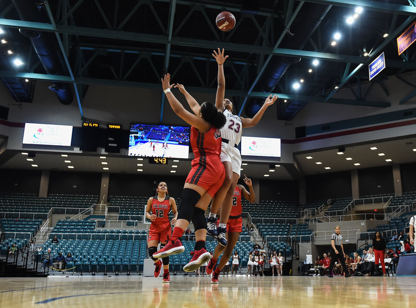 Katy Tx. Feb. 18, 2020: Tompkins' Loghan Johnson (23) goes up for the shot guarded by Fort Bend Travis Amari Grace (20) during a bi-district playoff game between Tompkins Falcons and Fort Bend Travis Tigers at the Merrell Center.  (Photo by Mark Goodman / Katy Times)